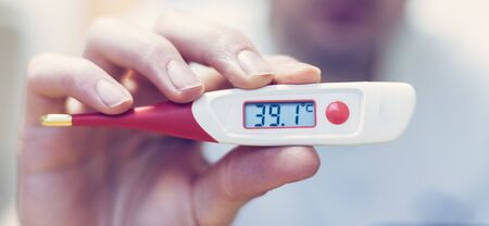 Man is holding a red fever thermometer in his hand