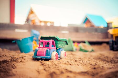Children plastic toys in the sand box. Truck, selective focus. 免版税图像