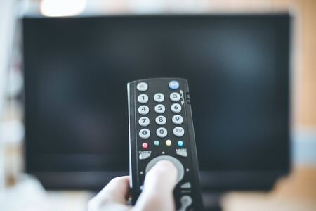 TV remote control in the foreground, tv in the blurry background.