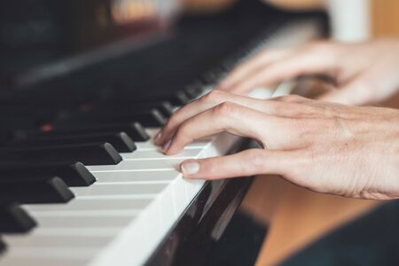 Man is playing piano at home. Clipping of piano and hands.
