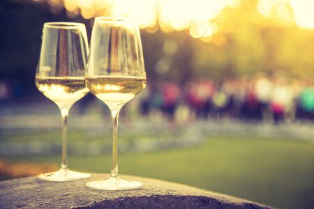 Glass of white wine on a stone wall in the formal garden. Enjoying it in the own garden in the evening sun. Stock Photo