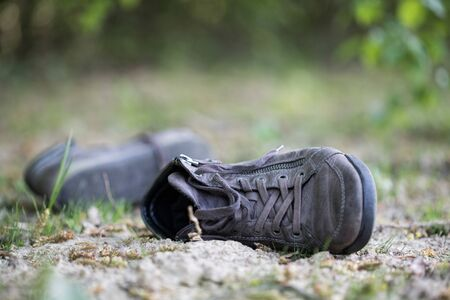 Dusty old shoe abandoned in the nature. Concept for missing.