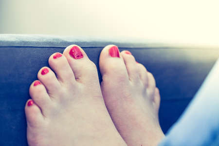 Close up of female feet with red nail polish on a blue couch