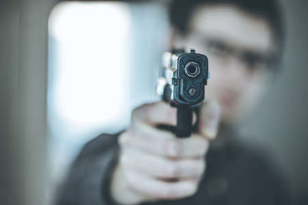 Robber or criminal is aiming with a black gun, blurry face