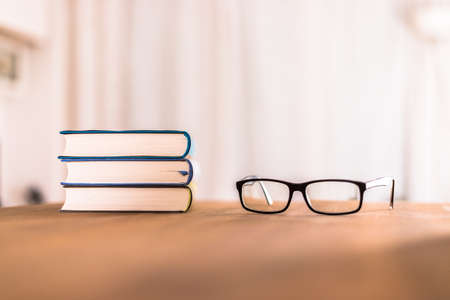 Stack of books and glasses lying on wooden desk at home. Knowledge and science Zdjęcie Seryjne
