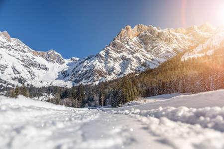 Beautiful idyllic winter landscape with footpath, stunning mountain range, snowy trees and blue sky