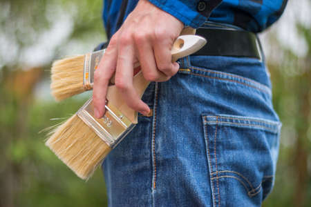 Close up picture of a craftsman with paint brushes in his pocket 스톡 콘텐츠