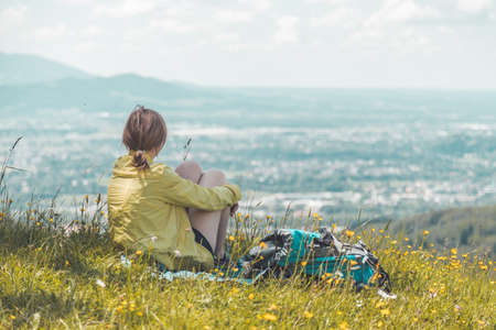 Sporty girl on a hiking trip is sitting on the meadow an enjoying the view over the far away city