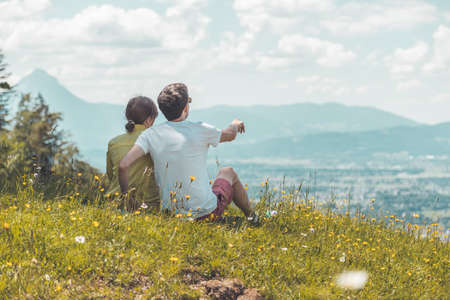 Couple on a hiking trip is sitting on the meadow an enjoying the view over the far away city