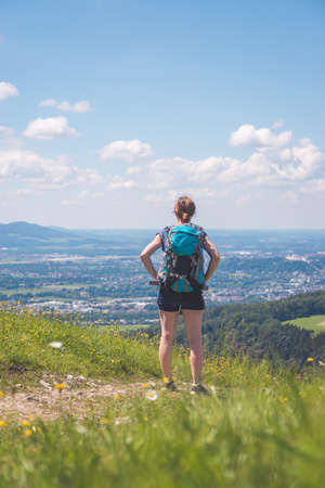 Sporty girl on a hiking trip is standing on the meadow an enjoying the view over the far away city