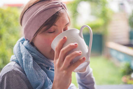 Young Caucasian woman is enjoying a cup of tea on the veranda