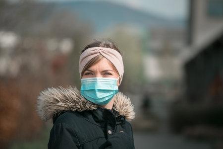 Young woman outdoors wearing a face mask. Corona and flu season.