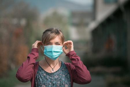 Young woman outdoors putting on face mask. Corona and flu season. Standard-Bild