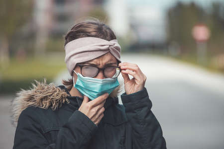 Young woman outdoors wearing a face mask and glasses, tarnished glasses Imagens