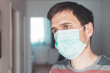 Young man indoor wearing a face mask, portrait. Corona and flu season.