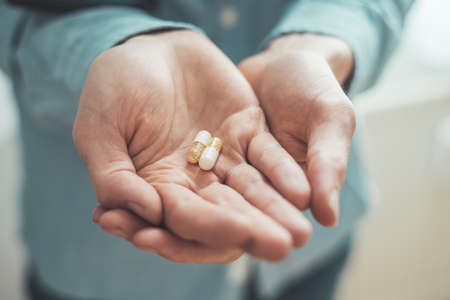 Male hand holding drug or vitamin pill in