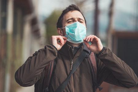 Young man outdoors putting on face mask. Corona and flu season.