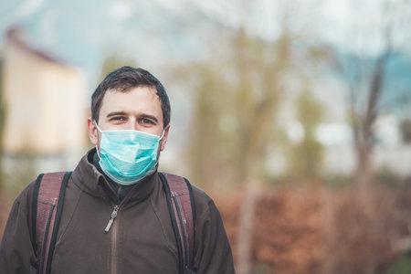 Young man outdoors wearing a face mask. Corona and flu season.