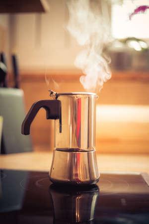 Italian coffee cooker on hot stove, breakfast