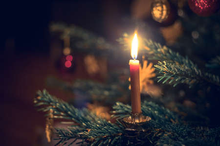 Candle on a branch of a decorated Christmas tree