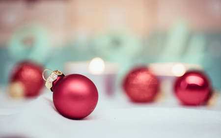 Christmas decoration: Close up of red Christmas baubles, advent calendar in the blurry background