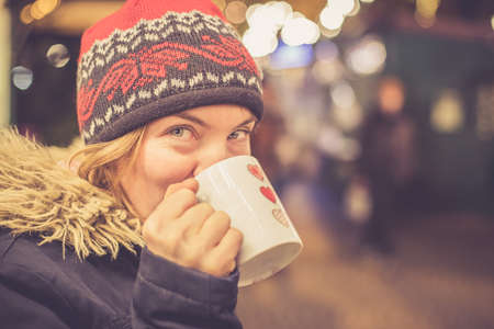 Girl is drinking mulled wine on the Christmas market, fun Standard-Bild
