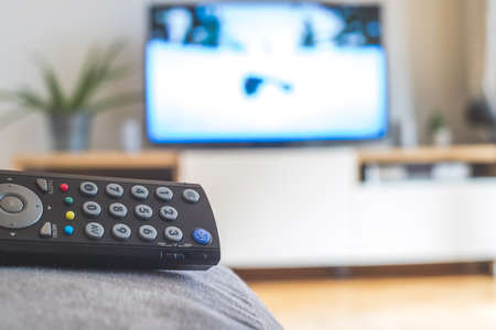 TV remote control in the foreground, tv in the blurry background. Streaming.