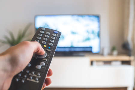 Holding a TV remote control in the hand, foreground, tv in the blurry background. Streaming.