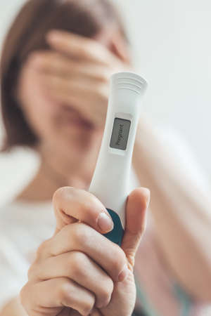Nervous Mother holding pregnancy test in her hands, result is pregnant,