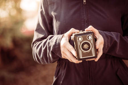 Girl is holding a vintage camera in her hands