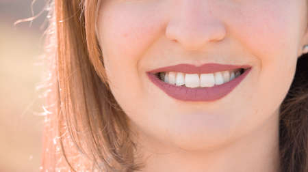 Beautiful girl with cherry red lips and white teeth is smiling
