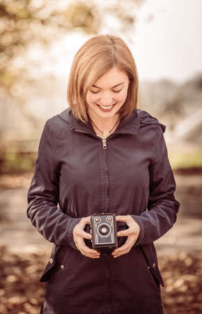 Cute girl is making pictures with a vintage camera, outside Imagens