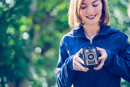 Cute girl is making pictures with a vintage camera, outside Standard-Bild