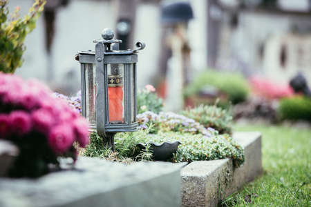 Candle in an iron lantern on a grave at a cemetery