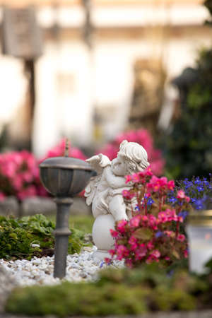 White angel on a grave at a cemetery, flowers