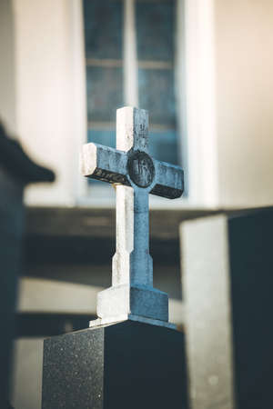 White Stone cross on a grave, evening sun