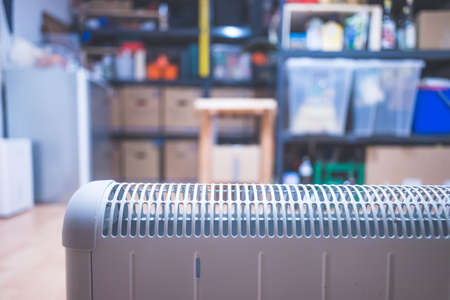 Electric heater, heating the basement. Blurry shelfs in the background