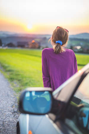 Young woman sitting on a car, enjoying the sunset