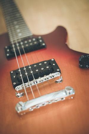 Electronic guitar in sunburst optic lying on the wooden floor