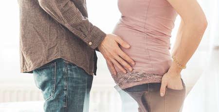 Close up of pregnant mother and father, hugging the tummy, Caucasian Archivio Fotografico