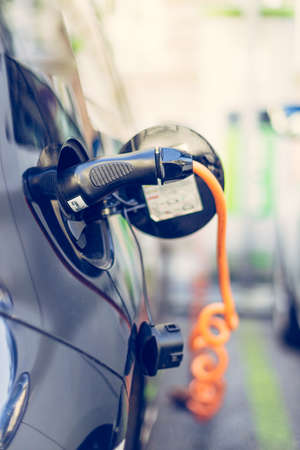 Electric car recharging with charge cable and plug leading to charge point.