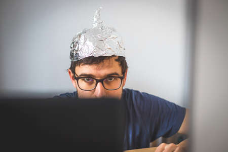 Young man is wearing aluminum cap, conspiracy theory concept