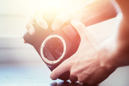 Hands of a photographer are touching a professional reflex camera, open sensor. Sunlight.