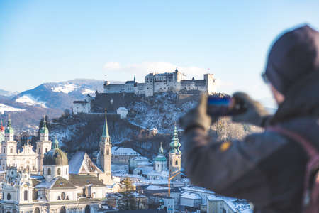 Young tourist man is making a photo of Salzburg with her smartphone, winter time