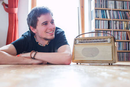 Young man listing to an retro radio