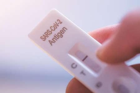 Close up of fingers holding express antigen covid test, negative result