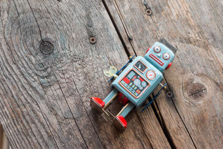 Robot toy, symbol for a chatbot or social bot and algorithms. Wood texture.