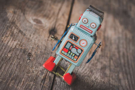 Robot toy, symbol for a chatbot or social bot and algorithms. Wood texture. Standard-Bild
