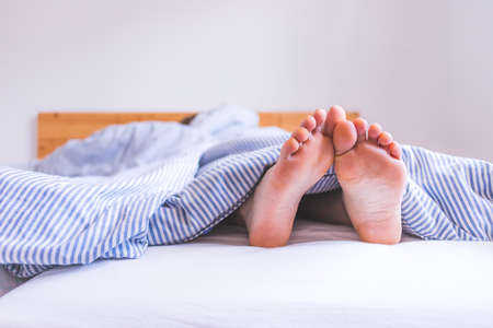 Close up uncovered female adult feet sleeping in bed, morning
