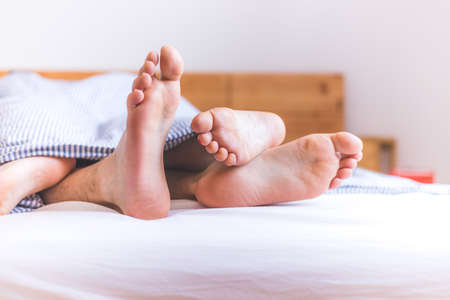 Close up a couples uncovered feet sleeping in bed, morning